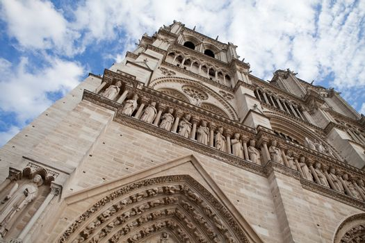 Famous landmark Gothic catholic cathedral Notre-dame on Cite island in Paris France on the blue and cloudy sky background