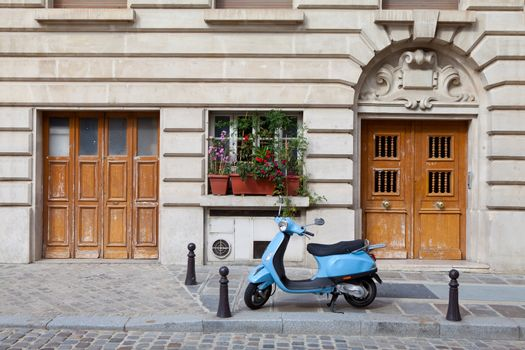 Blue retro motor bicycle parked between two wooden doors on sidewalk near old style house and cobblestone street in European town