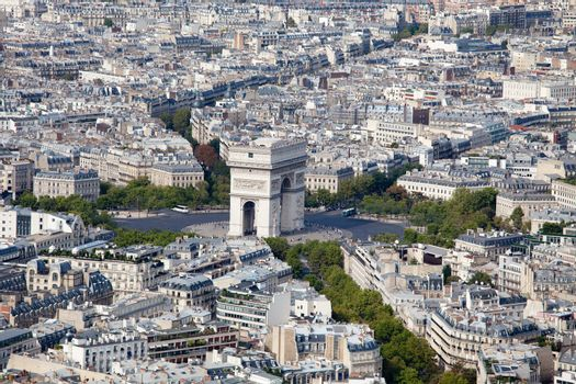 Top view on Triumphal Arch and Etoile square, roofs, housetops, city residential quarters and downtown, center streets in Paris France