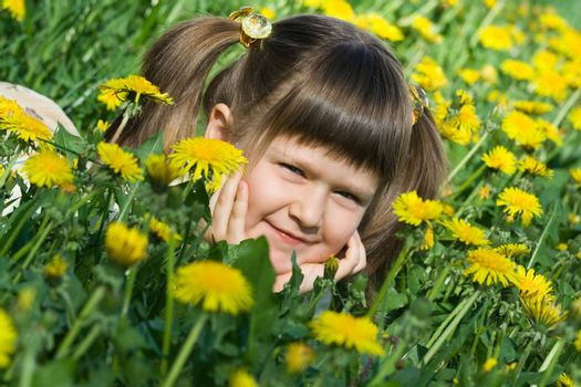 Little cool smiling girl is lying on the flowering dandelion meadow