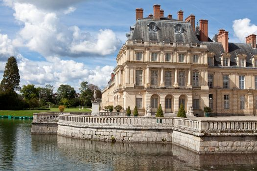 Medieval landmark royal hunting castle Fontainbleau near Paris in France and lake with white swans