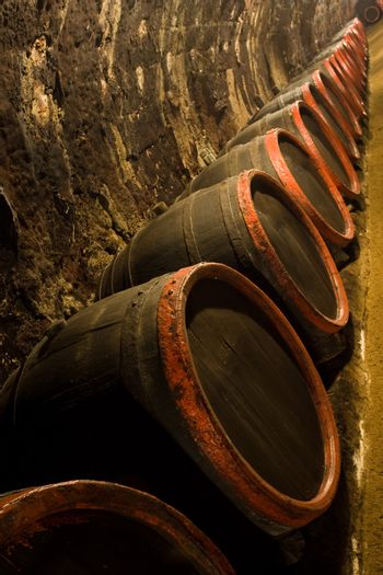 Row of Old wine barrels are stored in winery cellar near aged wall resedes into the distance