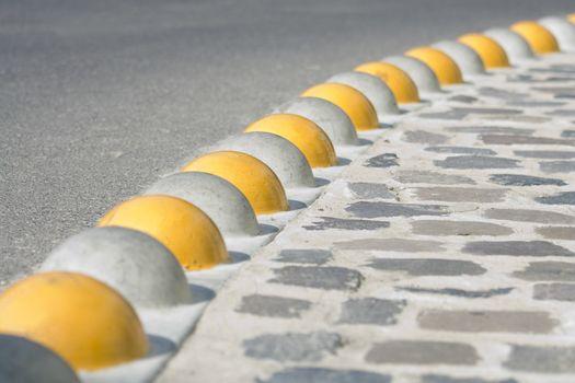Bent curb close-up separated asphalt road and cobblestone