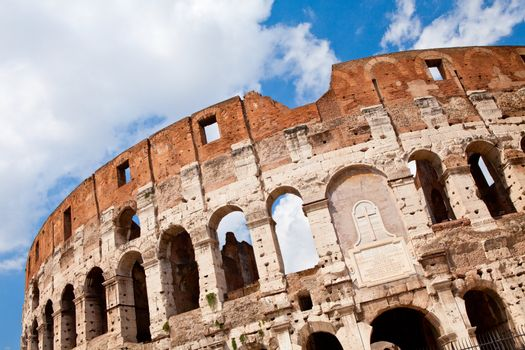Arched antique facade of ancient architectural European landmark gladiatorial amphitheatre Colosseum in Rome Italy on the blue sky background