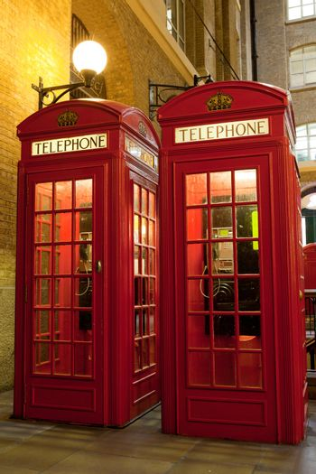 Traditional London symbol red public phone boxes at illuminated evening street. Great Britain