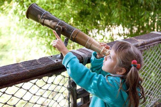 Little inquisitive girl preschooler discovers surroundings on observation balcony in spring park through old-style telescope and point a finger at finding