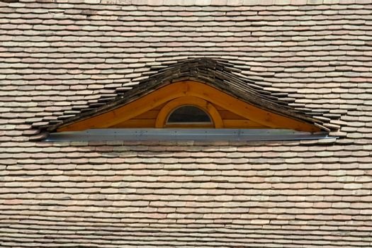 Attic wooden window on the tilled roof