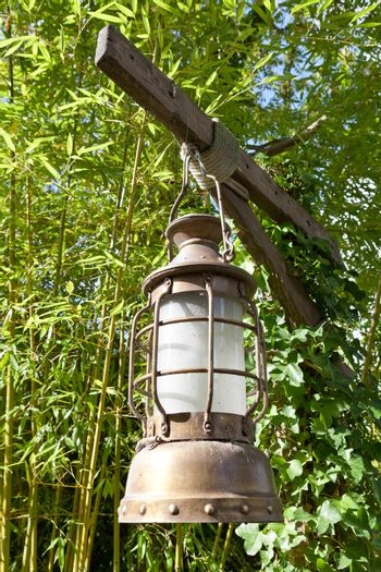 Street aged vintage copper kerosene oil lamp with glass bulb is hung up batten outside on the green leaves background