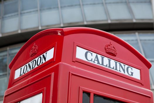 Traditional London symbol red public phone box for calling on the modern business center façade background