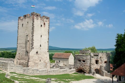Medieval aged stone Kinizsi castle and tower in Nagyvazsony, Hungary on the blue sky background and countryside surroundings