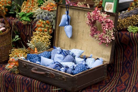 Dried wild flowers and cotton bags with lavender in old fashioned suitcase
