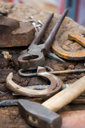 Horseshoes, nippers, hammer and other forging tools close-up