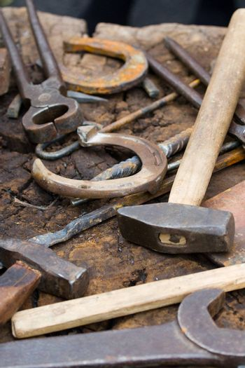 Rusty blacksmith tools and horseshoes on wooden log