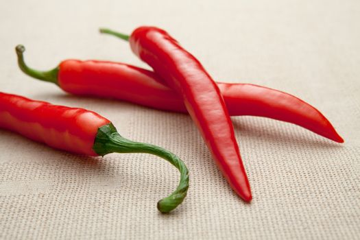 Fresh ripe pods of red hot cayenne chili pepper close-up on  beige homespun tablecloth