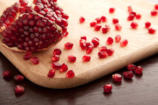 Pomegranate slices and seeds on wooden background