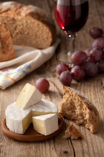 Piece and wheel of traditional Normandy soft cheese Camembert with country homemade bread, grapes and glass of red wine on wooden table