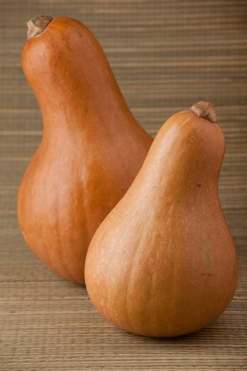 Group of ripe orange gourds on rural straw woven surface and stripy background