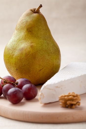 Close-up ripe green pear, piece of white soft cheese brie, core of Circassian walnut and red grapes on wooden board and linen tablecloth