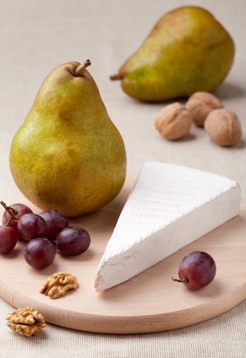 Ripe green pears, piece of white soft cheese brie, cores of Circassian walnuts and red grapes on wooden board and linen tablecloth