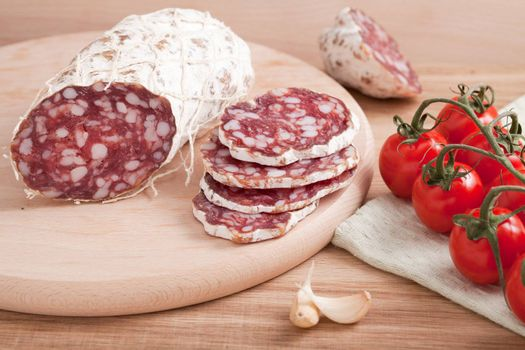 Traditional sliced salami on wooden board with garlic, cherry tomatoes