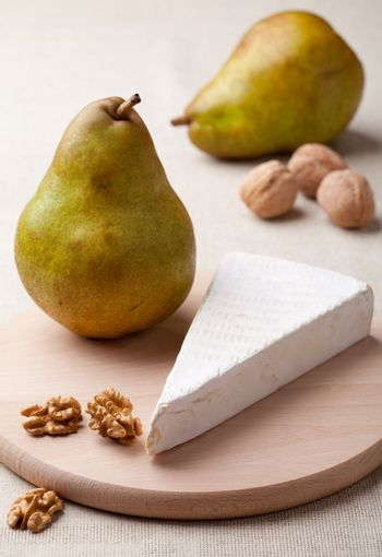 Ripe green pears, piece of white soft cheese brie, cores of Circassian walnuts on wooden board and linen tablecloth