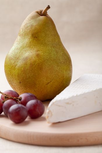 Close-up ripe green pear, piece of white soft cheese brie, red grapes on wooden board and linen tablecloth