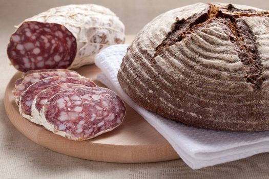 Close-up traditional sliced meat sausage salami on wooden board with loaf of homemade brown bread  on textile towel