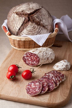 Traditional sliced salami on wooden board, fresh cherry tomatoes brown bread loaf in wicker breadbasket