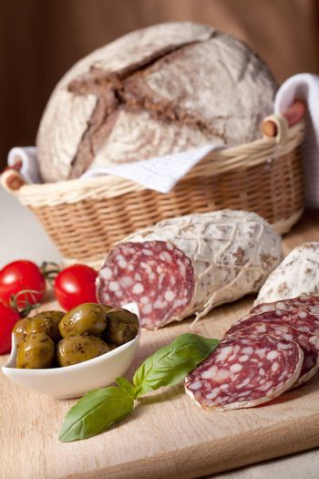 Traditional sliced salami on wooden board, fresh cherry tomatoes, green olives in salad bowl, brown bread loaf in wicker breadbasket