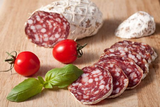 Traditional sliced meat sausage salami on wooden board with basilic and red bunch of cherry tomatoes