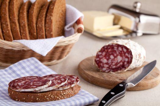 Served kitchen table, sandwich on napkin, salami on wooden board and knife, dairy butter in metal butterdish, sliced brown bread in wicker breadbasket