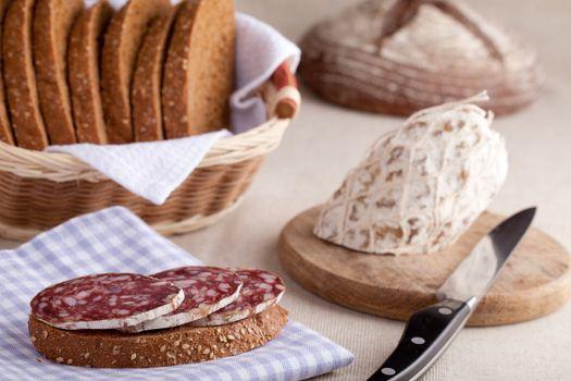 Served kitchen table, sandwich on napkin, salami on wooden board and knife, loaf, sliced brown bread in wicker breadbasket