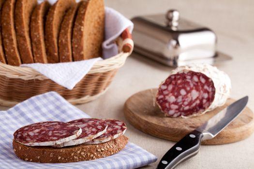 Served kitchen table, sandwich on napkin, salami on wooden board and knife, metal butterdish, sliced brown bread in wicker breadbasket