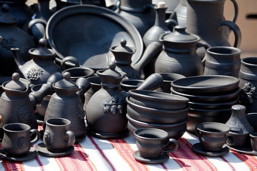 Rustic handmade black ceramic pottery souvenirs (plates, bowls, teapots, cups) on embroidered traditional Ukrainian towel at street handicraft market