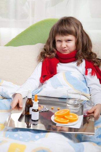 Sympathetic little sick girl with wry face in red scarf under blanket in bed is taking a salver with pills, sprays and orange