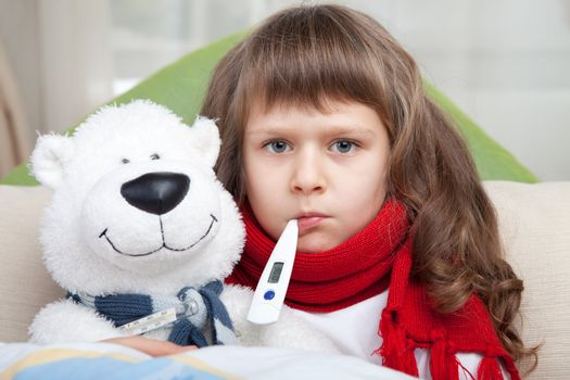 Sympathetic little sick girl with red scarf and clinical thermometer in mouth embraces white toy bear under blanket in the bed