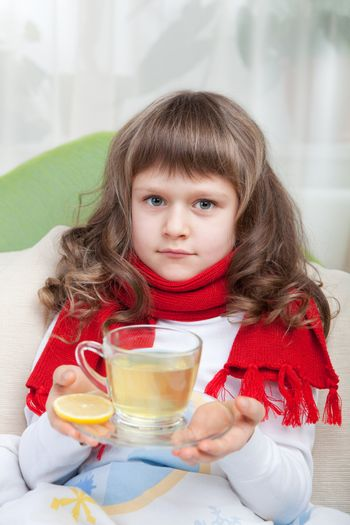Close-up sympathetic little sick girl wrapped in red scarf under blanket in bed is drinking antiviral with lemon slice from transparent cup
