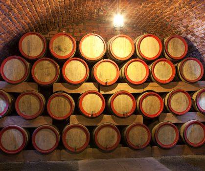 Wooden wine barrels are stored in winery cellar close-up