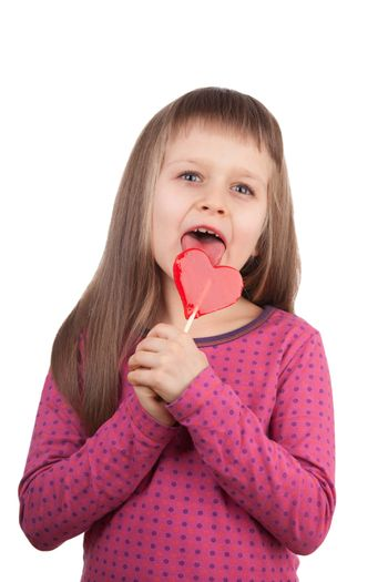 Portrait of little cute happy girl 7-8 years old licking red sweet lollipop in the shape of heart isolated