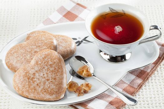 Served cookies heart shape, crystal brown sugar in silver spoon, black tea in cup on saucer on plaid textile tablecloth
