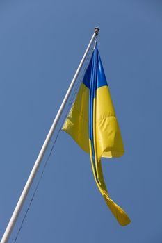 Waving Ukrainian Yellow-Blue Flag hoisted on flagpole on the blue sky background