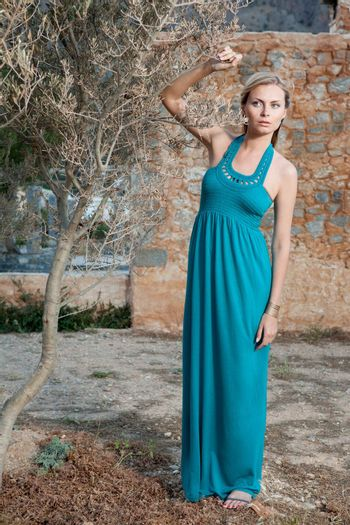 Portrait of romantic gentle elegant young blond woman with blue eyes and dress, near olive tree on the Mediterranean style court and stone wall background