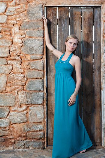 Portrait of romantic gentle elegant young blond woman with blue eyes and dress on the Mediterranean style court, wooden door and  stone wall background