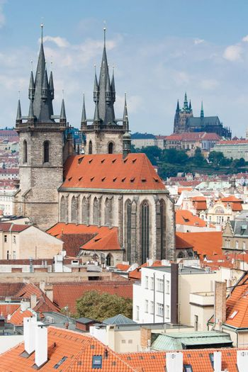 Top view cityscape on red tiled mansard roofs, old district, Gothic cathedral of Virgin Mary before Tyn and Prague castle on blue sky background