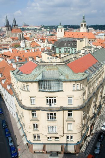 Top view cityscape on facades, red tiled mansard roofs, old Prague streets and district, Gothic cathedrals on blue sky background