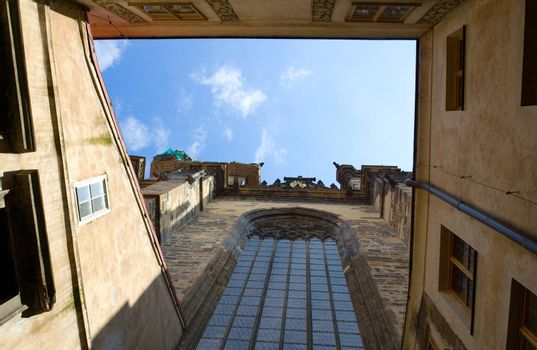 View on blue cloudy sky from inner encloused court of stone catholic gothic church of Virgin Mary Before Tyn with round-headed glass window in Prague Czech Republic