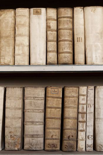 Hard covers of rust moldy ancient books monuscripts on wooden shelves in bookcase