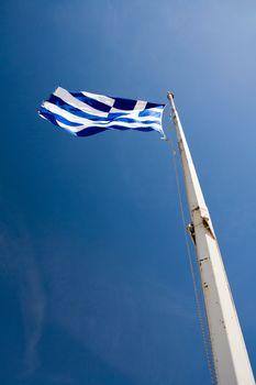 Flying Greek Flag hoisted on flagpole on the blue sky background