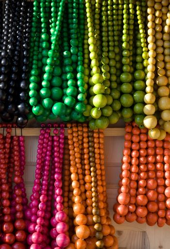 Showcase of handicraft wooden many-colored beads on the craft market close-up