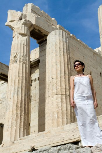 Close-up young woman dressed white near the columns of entrance propylaea to ancient temple Parthenon in Acropolis Athens Greece on blue sky background